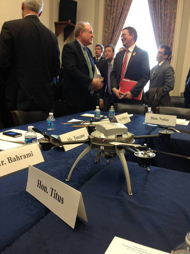"Members of the House Transportation and Infrastructure Committee get a close look at this four-rotor drone during a ""roundtable discussion"" meeting on Capitol Hill in Washington, Wednesday, March 5, 2014, with industry and Federal Aviation Administration (FAA) officials on how best to integrate small drones into the national airspace."