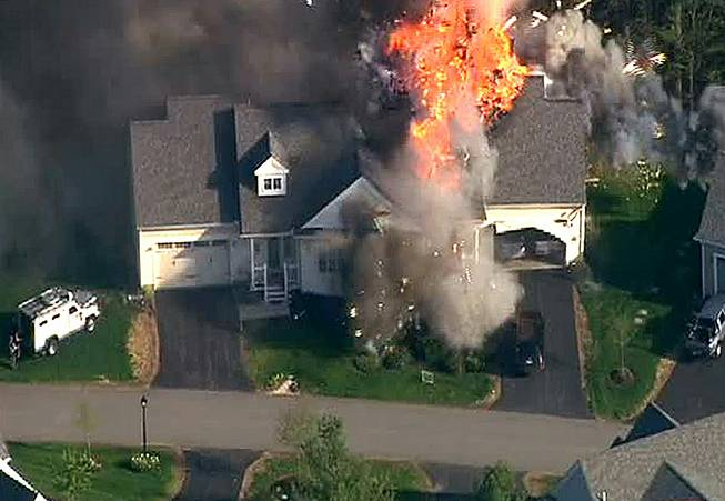 In this frame grab from television helicopter video, a police SWAT team, left, is parked on the lawn of a home in Brentwood, N.H., as it explodes in flames, Monday May 12, 2014. Shots were fired just before the fire, which involved a police officer.