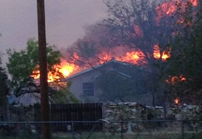 In this Sunday, May 11, 2014 photo provided by the Texas Department of Public Safety, a wildfire burns near Fritch, Texas. The wildfire has led to evacuations and road closures and has destroyed dozens of homes.