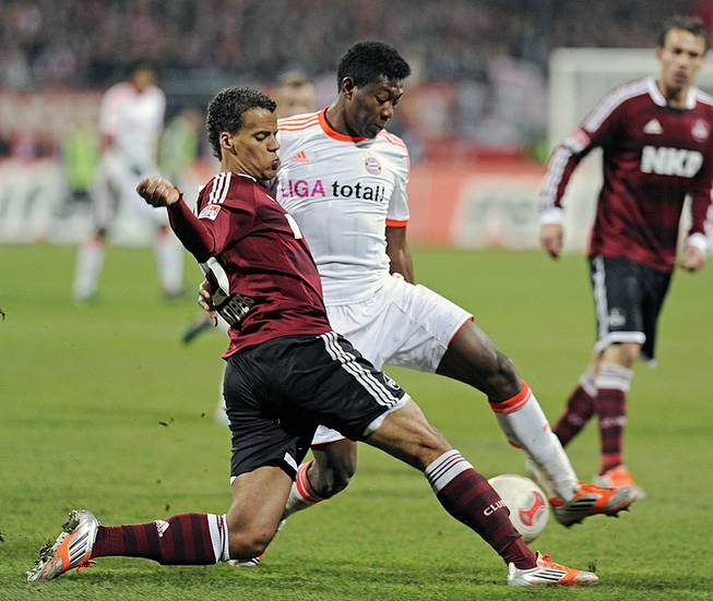 Nuremberg's Timothy Chandler of the U.S., left, and Bayern's David Alaba of Austria challenge for the ball during a soccer match in Nuremberg, Germany, Nov. 17, 2012.