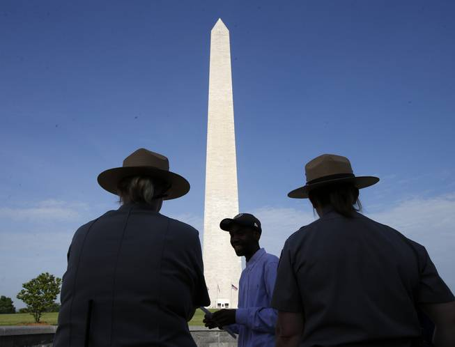 Park Service employees stand watch as visitor Roman Tanner, center, walks away with his Washington Monument ticket, which are distributed at on a first-come basis at the Washington Monument in Washington, Monday, May 12, 2014, ahead of a ceremony to celebrate its re-opening.