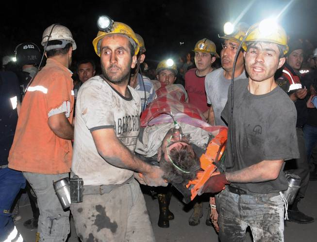 Miners carry a rescued miner after an explosion and fire at a coal mine killed at least 17 miners and left up to 300 workers trapped underground, in Soma, in western Turkey, Tuesday, May 13, 2014, a Turkish official said.