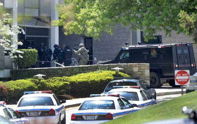 Police officers enter WMAR-TV, after a truck driven by a man rammed the Baltimore-area television station Tuesday, May 13, 2014 leaving a gaping hole in the front of the building, in Towson, Md.