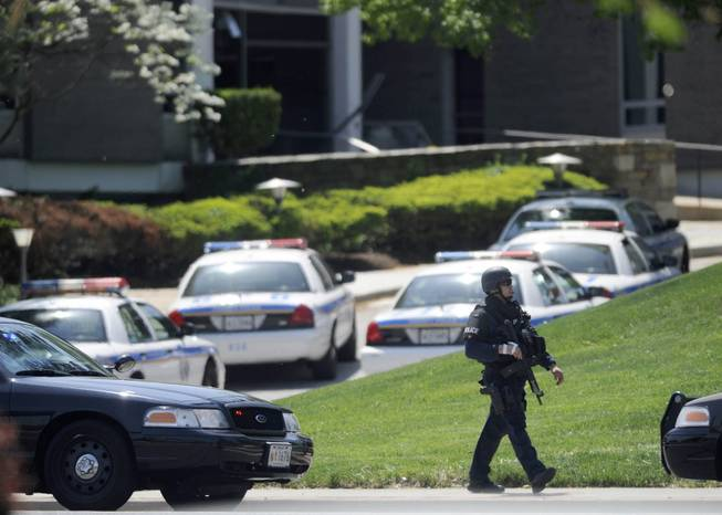A police officer walks near WMAR-TV, after a truck driven by a man rammed the Baltimore-area television station Tuesday, May 13, 2014 leaving a gaping hole in the front of the building, in Towson, Md.