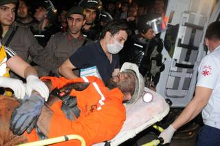 Medics place a rescued miner into an ambulance after an explosion and fire at a coal mine killed at least 17 miners and left up to 300 workers trapped underground, in Soma, in western Turkey, Tuesday, May 13, 2014, a Turkish official said.