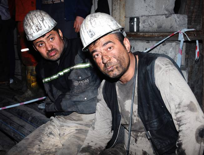 Two miners look around after being rescued hours after an explosion and fire at a coal mine killed at least 17 miners and left up to 300 workers trapped underground, in Soma, in western Turkey, late Tuesday, May 13, 2014, a Turkish official said.