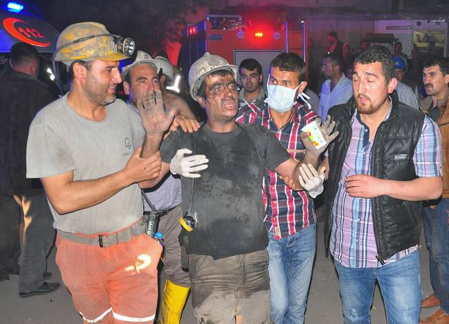 Miners escort a rescued friend after an explosion and fire at a coal mine in Soma, in western Turkey, Tuesday, May 13, 2014.