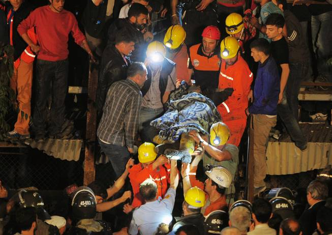 Miners carry a rescued friend hours after an explosion and fire at a coal mine killed at least 17 miners and left up to 300 workers trapped underground, in Soma, in western Turkey, late Tuesday, May 13, 2014, a Turkish official said.