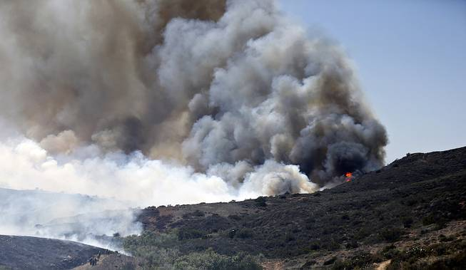 Billowing smoke rises from flames as firefighters begin the trek up the hills to battle a wild fire, Tuesday, May 13, 2014, in San Diego.