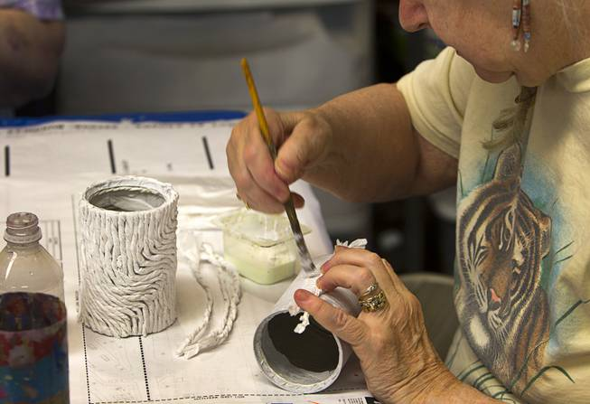 Volunteer Nancy David decorates a can during an art class at the Nevada Senior Services Adult Day Care Center of Las Vegas, 901 N. Jones Blvd., Wednesday, May 14, 2014. The artwork will be used as a menu holder at a restaurant.
