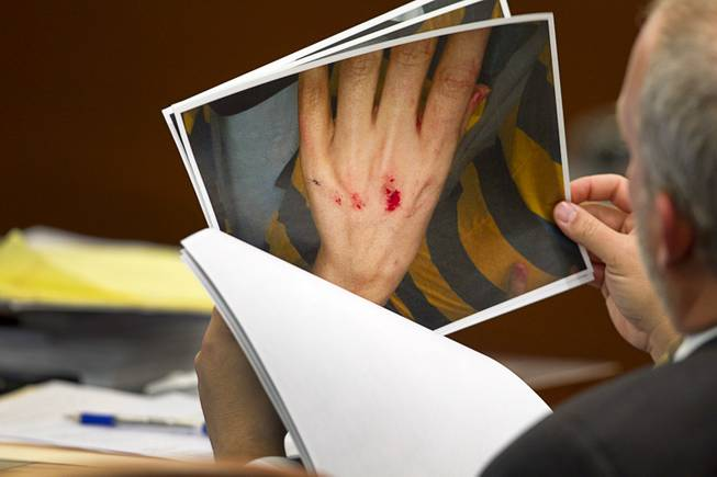"Prosecutor Marc DiGiacomo looks over defense photos during a trial for Jason Omar Griffith at the Regional Justice Center Wednesday, May 14, 2014. Griffith is accused of murdering Luxor ""Fantasy"" dancer Deborah Flores Narvaez in December 2010. The photos show injuries to Flores Narvaez after she broke Griffith's bedroom window."