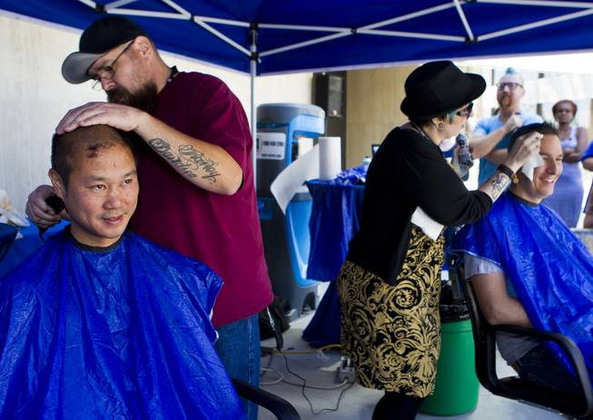 Zappos CEO Tony Hsieh joins other employees as they receive haircuts during the 10th Annual Zappos Bald and Blue charity event on Wednesday, May 15, 2014.