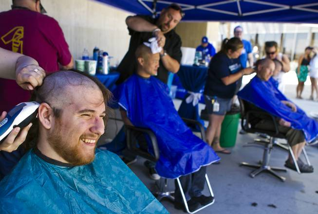 Zappos call center employee Robert Greeley joins others as they receive haircuts during the 10th Annual Zappos Bald and Blue charity event on Wednesday, May 15, 2014.