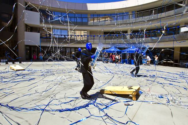 The Blue Man Group blast confetti as they celebrate the 10th Annual Zappos Bald and Blue charity event and unveiling of a collaborative, interactive art installation entitled ShoeZaphone on Wednesday, May 15, 2014.