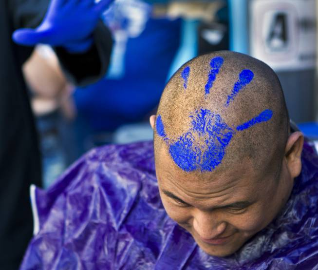 Zappos audio-visual team member Mikey Maneeraj shows off his fresh haircut and blue-paint hand stamp during the 10th Annual Zappos Bald and Blue charity event on Wednesday, May 15, 2014.