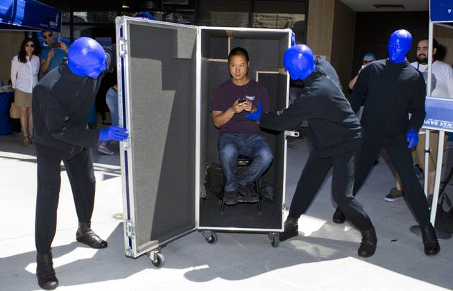 The Blue Man Group unveils Zappos CEO Tony Hsieh from within a rolling case during the 10th Annual Zappos Bald and Blue charity event on Wednesday, May 15, 2014.