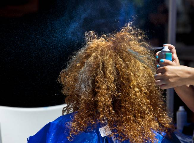 Blue hairspray is applied to strands of hair of a Zappos employee during their 10th Annual Zappos Bald and Blue charity event on Wednesday, May 15, 2014.