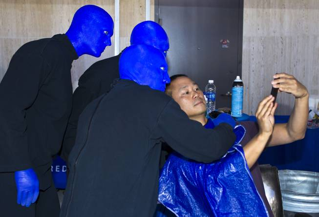 "The Blue Man Group poses with Zappos CEO Tony Hsieh for a ""selfie"" during the 10th Annual Zappos Bald and Blue charity event on Wednesday, May 15, 2014."