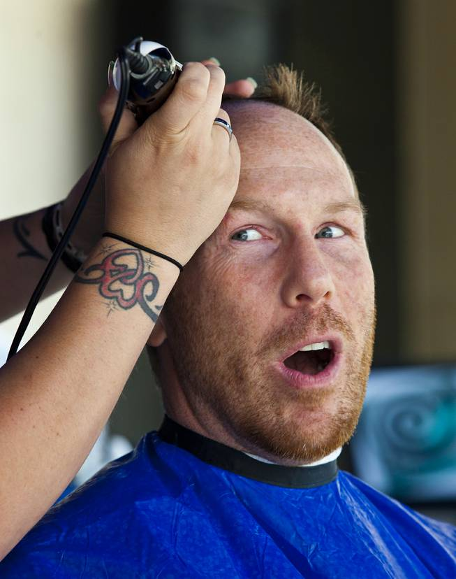 Luke Johnson with Zappos has his head shaved with many others during the 10th Annual Zappos Bald and Blue charity event on Wednesday, May 15, 2014.