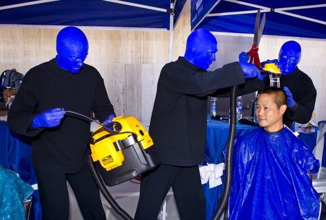 The Blue Man Group members joke with Zappos CEO Tony Hsieh as he readies for a haircut during the 10th Annual Zappos Bald and Blue charity event on Wednesday, May 15, 2014.