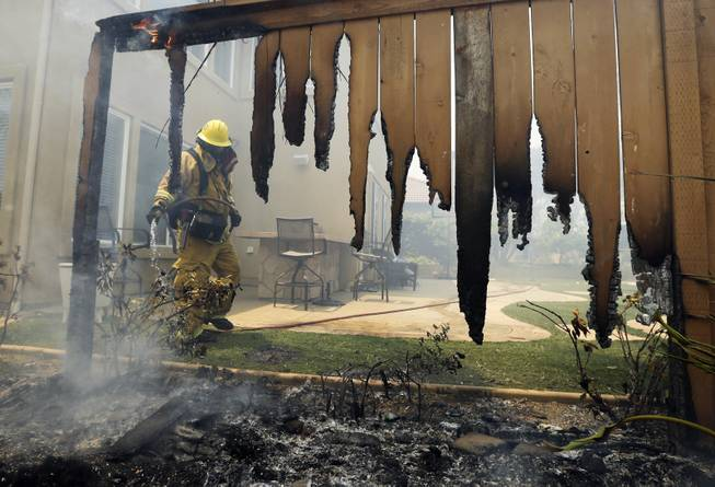 A Firefighter puts water on a house fence during a wildfire Wednesday, May 14, 2014, in Carlsbad, Calif. More wildfires broke out Wednesday in San Diego County  threatening homes in Carlsbad and forcing the evacuations of military housing and an elementary school at Camp Pendleton  as Southern California is in the grip of a heat wave. (AP Photo)