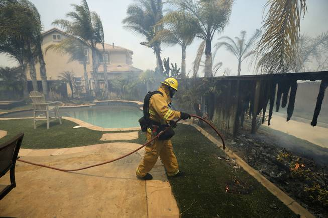 A Firefighter puts water on a house fence during a wildfire Wednesday, May 14, 2014, in Carlsbad, Calif. More wildfires broke out Wednesday in San Diego County  threatening homes in Carlsbad and forcing the evacuations of military housing and an elementary school at Camp Pendleton  as Southern California is in the grip of a heat wave.