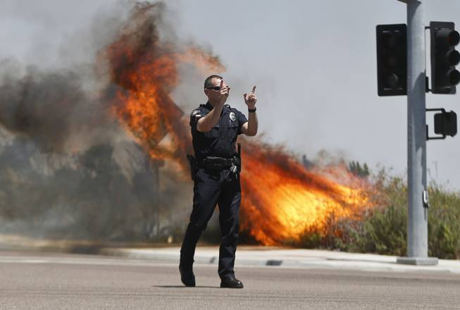 A Carlsbad,Calif. police officer turns traffic away as flames leap behind him Wednesday, May 14, 2014, in Carlsbad, Calif.  Weather conditions that at least temporarily calmed allowed firefighters to gain ground early Wednesday on a pair of wildfires that forced thousands of residents to leave their homes.