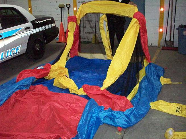 This May 13, 2014, photo provided by the South Glens Fall Police Department, shows a deflated bounce house that three children were playing in on Monday when it broke loose from plastic anchoring stakes and was swept skyward by gusty winds, in South Glens Fall, N.Y.