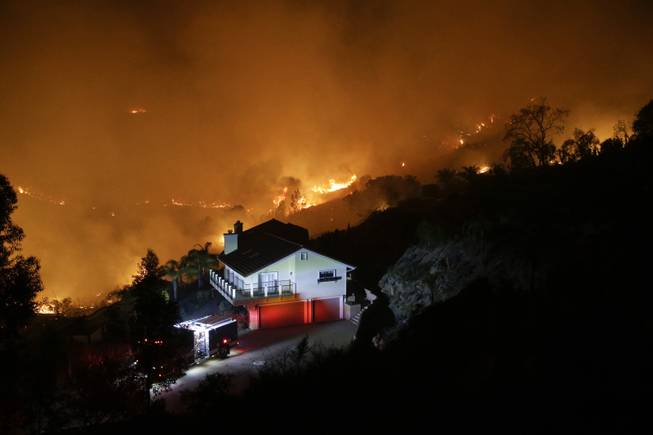 AP10ThingsToSee - A wildfire burns near a home on Wednesday, May 14, 2014, in San Marcos, Calif. Flames engulfed suburban homes and shot up along canyon ridges in one of the worst of several blazes that broke out Wednesday in Southern California during a second day of a sweltering heat wave. (AP Photo)