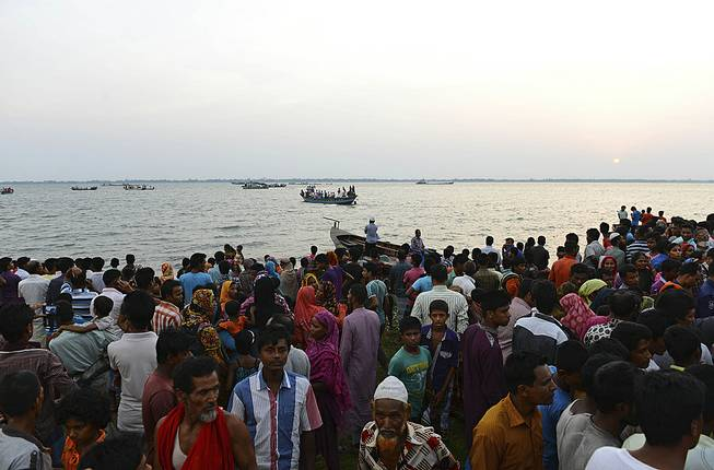 Bangladeshi people gather on the banks of the River Meghna after a ferry carrying more than 100 passengers capsized and sank after being hit by a storm in Munshiganj district, Bangladesh, Thursday, May 15, 2014.