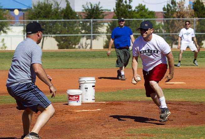 Sean McCrady, right, Las Vegas regional sales director for Winder Farms, reacts as Tim Hanko pretends to charge the mound during a casual Sunday baseball game at Red Ridge Park May 11, 2014.