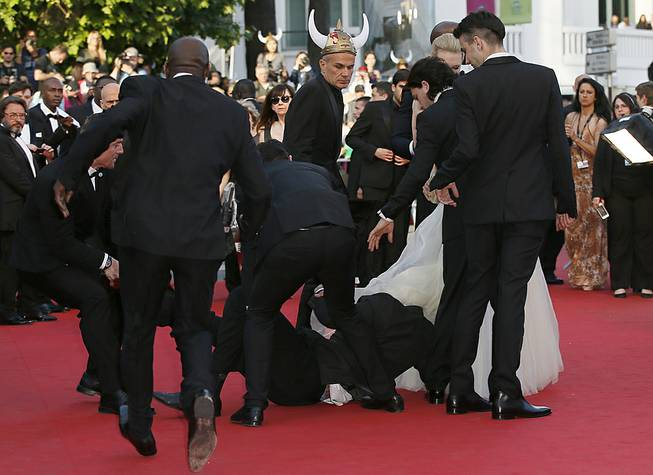 "Security run toward an unidentified man who ran unauthorized onto the red carpet during arrivals for the screening of ""How to Train Your Dragon 2"" at the 67th Cannes International Film Festival in Cannes, France, on Friday, May 16, 2014."
