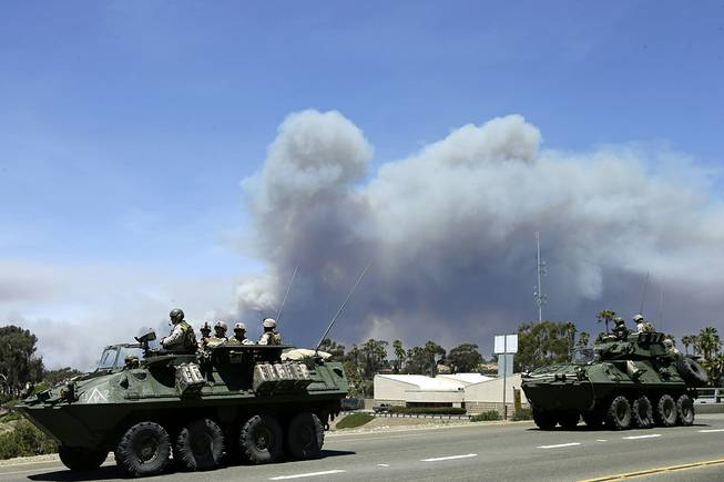 Marines move military vehicles near the entrance to Marine Corps Camp Pendleton in front of smoke plumes from the Las Pulgas wildfire burning on base Friday, May 16, 2014, in Oceanside, Calif.