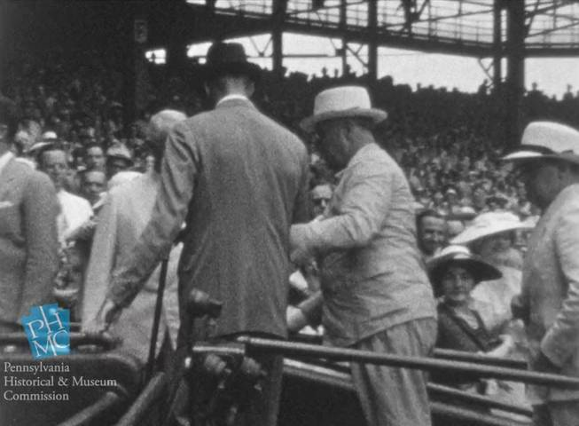 In this image taken from film shot by former Major League Baseball player Jimmie DeShong and acquired by the Pennsylvania Historical & Museum Commission, President Franklin D. Roosevelt, center right, walks to his seat with the aid of an assistant at the Major League Baseball All-Star game on July 7, 1937, at Griffith Stadium in Washington.