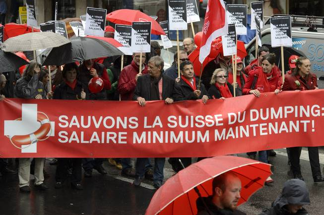 "In this picture taken May 1, 2014, demonstrators carry a banner reading ""Let's save Switzerland from dumping: wage minimum now!"" in Geneva, Switzerland."