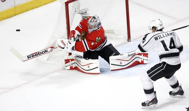 Chicago Blackhawks goalie Corey Crawford (50) clears the puck away from Los Angeles Kings right wing Justin Williams (14) during the second period of Game 1 of the Western Conference finals in the NHL hockey Stanley Cup playoffs in Chicago on Sunday, May 18, 2014.