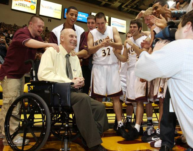This Jan. 10, 2009, file photo shows Northern State University men's basketball coach Don Meyer, second from left, smiling as he celebrates his 903rd career victory in Aberdeen, S.D. Meyer, one of the winningest coaches in college basketball who came back from a near-fatal car accident and liver cancer before closing out his career, died Sunday, May 18, 2014, in South Dakota. He was 69.