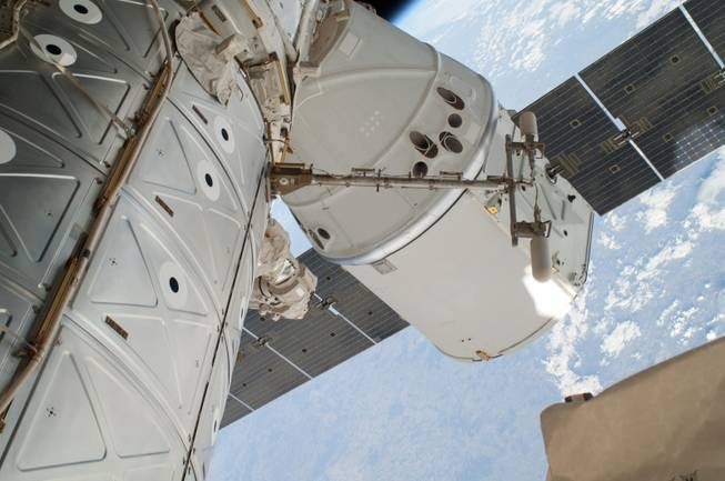 This April 22, 2014 file photo provided by NASA shows a photo of the SpaceX Dragon spacecraft docked to the International Space Station and was photographed by one of two spacewalking astronauts. On Sunday, May 18, 2014, after a one-month visit, the SpaceX cargo ship was for return to Earth. The astronauts released it using the International Space Station's big robot arm.