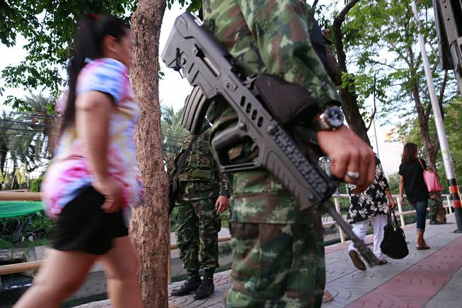 Pedestrians stroll past armed Thai soldiers guarding outside the Centre for the Administration of Peace and Order (CAPO) after soldiers were sent in to seize the center Tuesday, May 20, 2014 in Bangkok, Thailand.