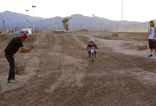 Thomas Ramirez, left, of Las Vegas, gives encouragement to his son on the pee-wee course at Sandy Valley MX in Sandy Valley Thursday, May 15, 2014. Ramirez said both his sons Thomas Jr, 7, and Ryder, 4, ride motocross.