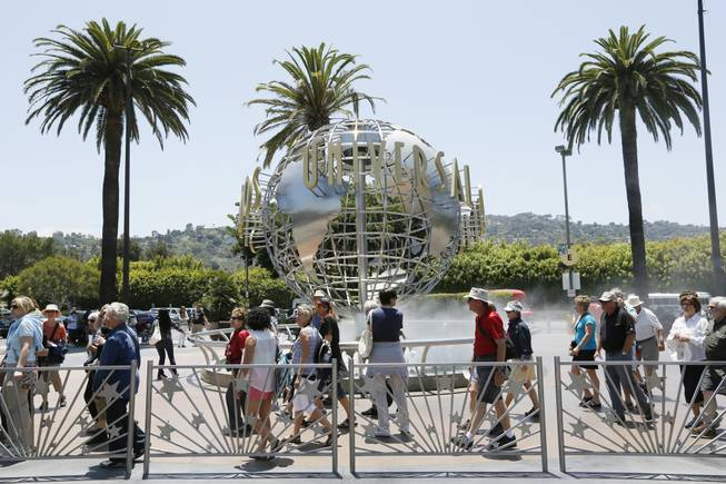 This photo taken Wednesday, June 5, 2013, show tourists lining up at the normal line at Universal Studios Hollywood in Los Angeles.