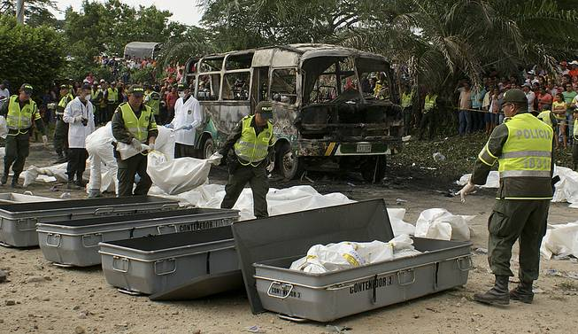 Police carry bags containing the remains of children who burned to death in the bus parked behind in Fundacion in northern Colombia, Sunday, May 18, 2014.