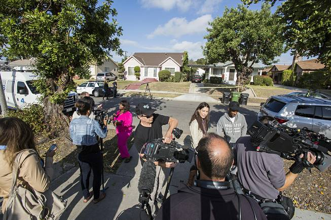 Neighbors are interviewed by media in front of the home of actor Michael Jace on Tuesday, May 20, 2014, in Los Angeles.