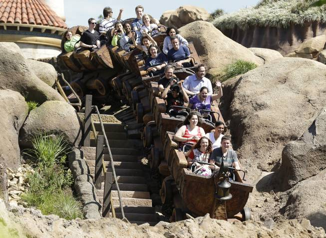 This May 16, 2014, photo shows Disney cast members testing the new Seven Dwarfs Mine Train roller coaster in the Magic Kingdom at Walt Disney World in Lake Buena Vista, Fla. The ride will be opened to park guests May 28.