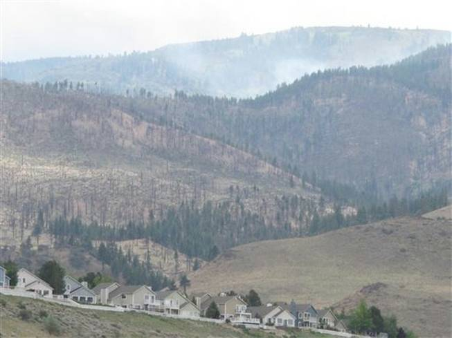 Houses are pictured in the foothills Monday, May 19, 2014, several miles from a wildfire burning to the west in the Mount Rose Wilderness Area along the Sierra's eastern front in Reno, Nev. Firefighters got the upper hand on the blaze Monday and no homes were threatened.In the background are trees recovering from a previous fire that burned much closer to houses in the Hunter Lake area.