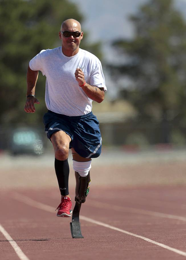 Mstr. Sgt. Christopher Aguilera runs at the outdoor track at Nellis Air Force Base Wednesday, May 21, 2014. Aguilera was selected as one of 40 Air Force members to participate in the 2014 London Invictus Games for wounded veterans. Aguilera was injured when his helicopter was shot down in Afghanistan in 2010.