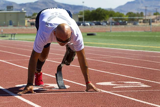 Mstr. Sgt. Christopher Aguilera is shown in the start position at the outdoor track at Nellis Air Force Base Wednesday, May 21, 2014. Aguilera was selected as one of 40 Air Force members to participate in the 2014 London Invictus Games for wounded veterans. Aguilera was injured when his helicopter was shot down in Afghanistan in 2010.
