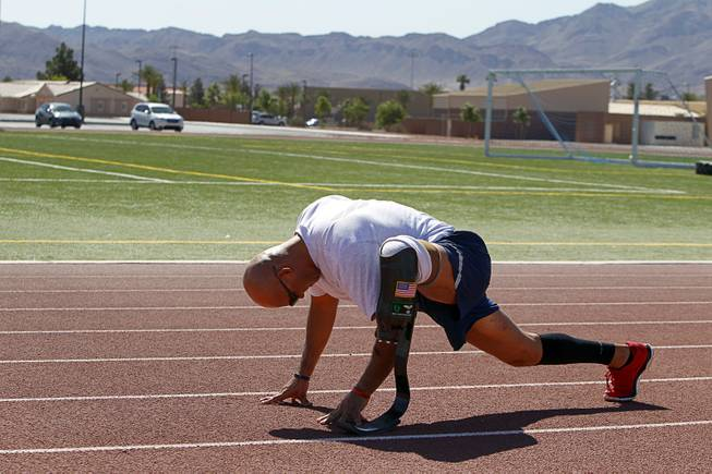 Mstr. Sgt. Christopher Aguilera stretches out at the outdoor track at Nellis Air Force Base Wednesday, May 21, 2014. Aguilera was selected as one of 40 Air Force members to participate in the 2014 London Invictus Games for wounded veterans. Aguilera was injured when his helicopter was shot down in Afghanistan in 2010.