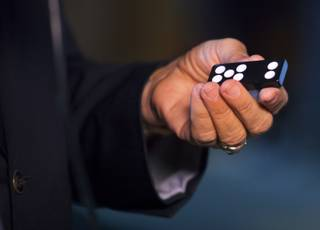 George Joseph shows off an opaque domino during a Courtroom Conversation at the National Museum of Organized Crime and Law Enforcement on Wednesday, May 21, 2014.  The MOB Museum is playing host for