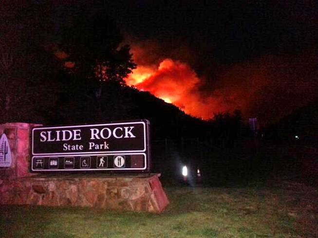 In this photo released by the Arizona Department of Public Safety, flames from a wildfire rise over a ridge behind the popular Slide Rock State Park Oak Creek Canyon near Sedona, Ariz., Tuesday, May 20, 2014.